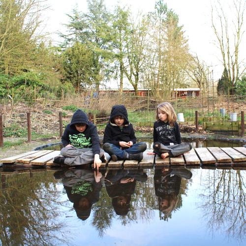 Studenten in De Eetbare Tuin, een gedeelte van de buitenruimte.